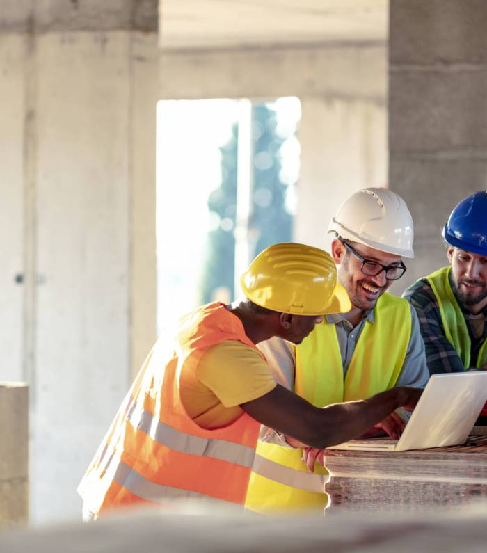 Team of Multi-Ethnic construction workers wearing protective helmets and vests discussing project details with executive supervisor standing with tools and laptop.
