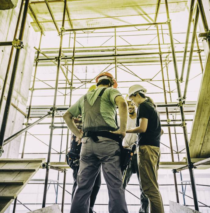 Three people with helmets, female architect, foreman and construction worker discussing about problem on a construction site, copy space.